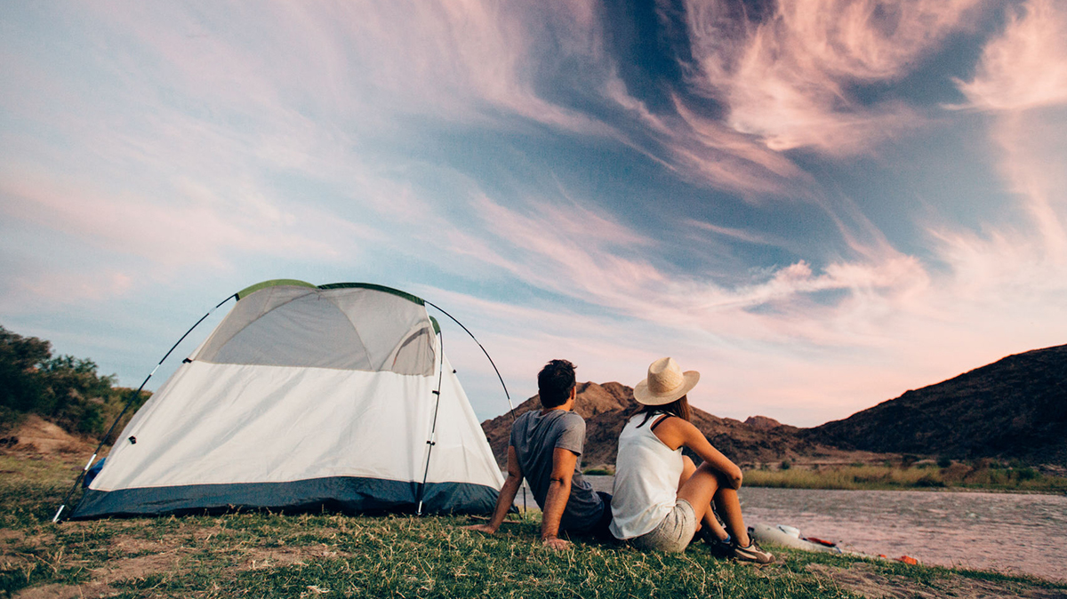 Man and woman sitting next to a tent