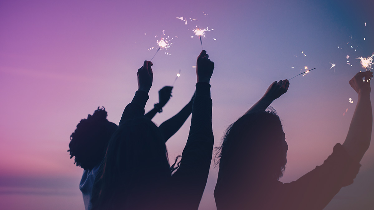 People holding sparklers at sundown