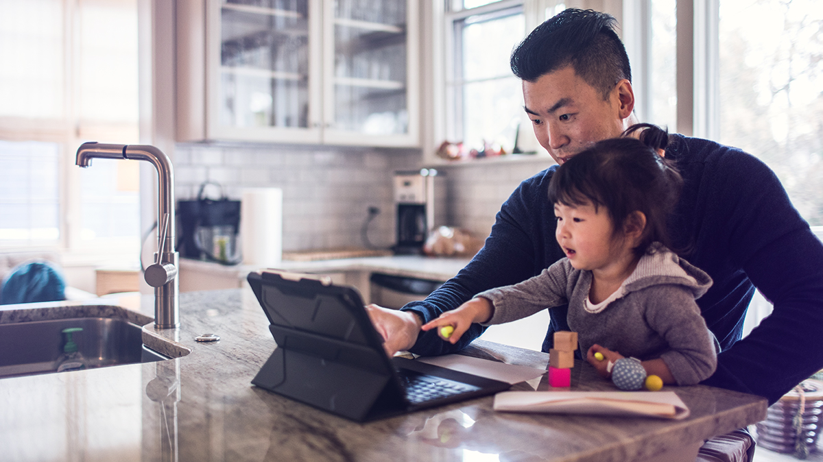 Father and daughter looking at a laptop