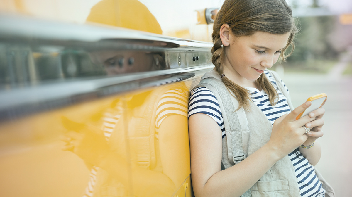 Girl leaning against a school bus, looking at her phone