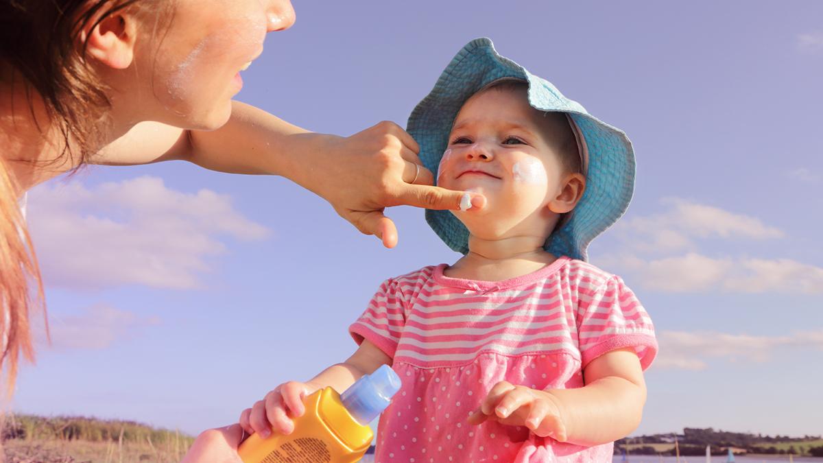 Mom putting sunscreen on baby