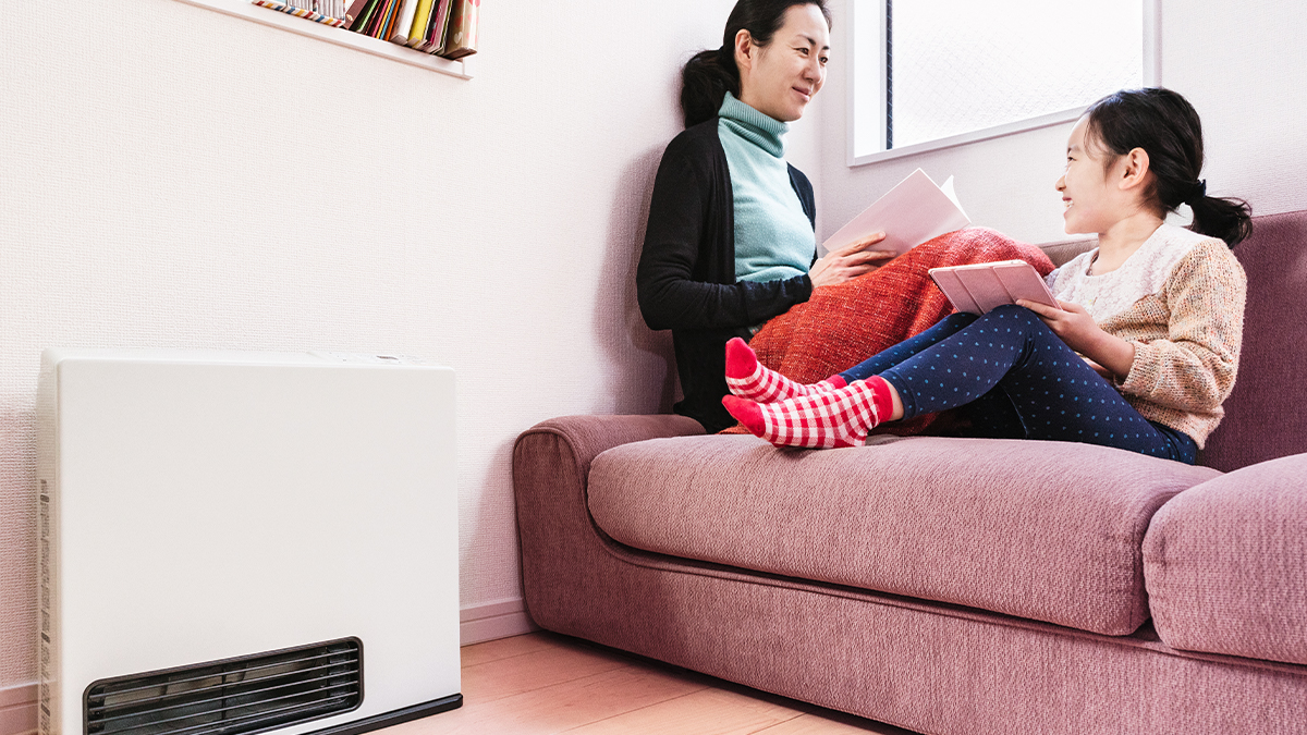 Woman and little girl with a space heater