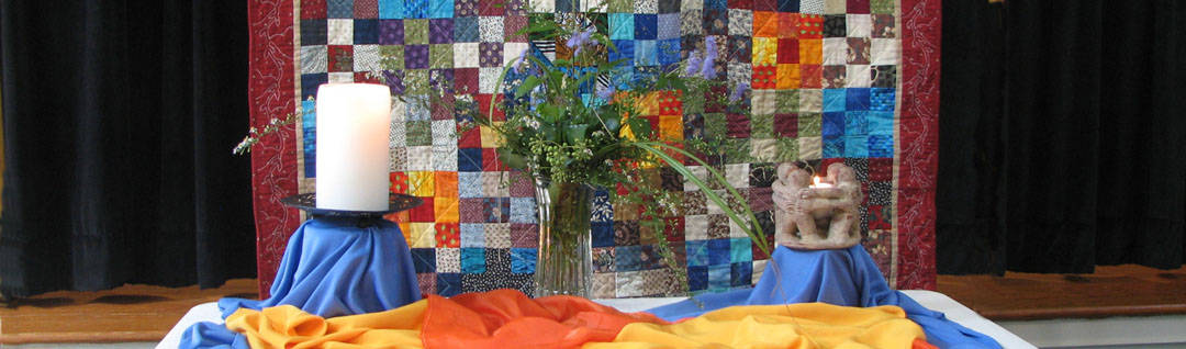 Worship table with candles in front of the community quilt.