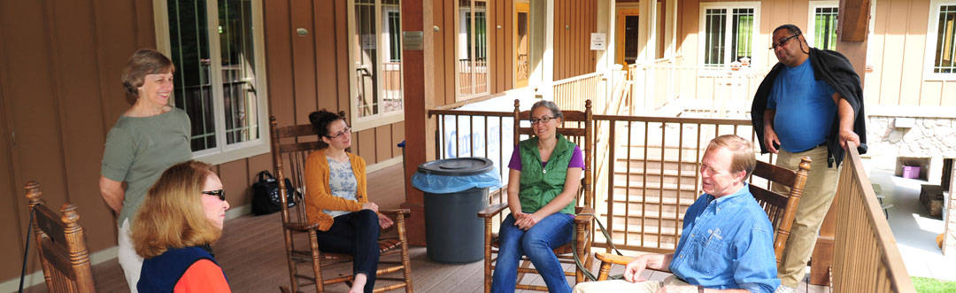 RMCers sitting in rocking chairs on the porch at Camp Agape.