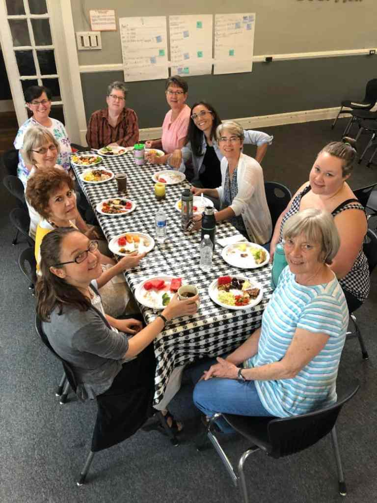 Folks at the fall 2019 worship retreat enjoy lunch together around the table.