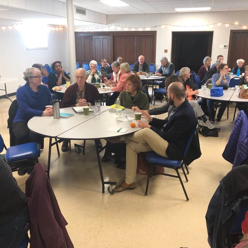 Group of people around tables at the pop-up seminary on Feb. 15, 2020.