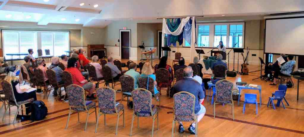 congregation sitting in chairs facing Melissa who is preaching at the front of the hall.