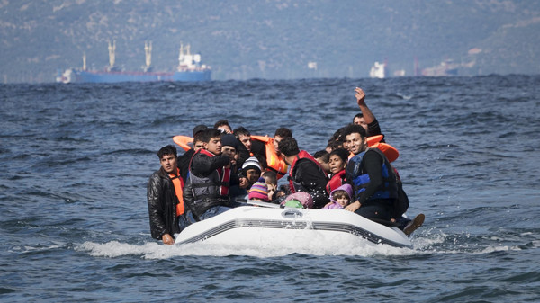 Lesbos, Greece - October 25, 2015: An inflatable boat filled with refugees and other migrants approaches the north coast of the Greek island of Lesbos. Turkey is visible in the background. More than 500,000 migrants have crossed from Turkey to the Greek islands so far in 2015.