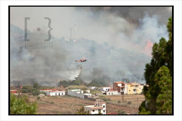 Un helicóptero contra incendios descarga agua en las proximidades de unas viviendas de Erjos