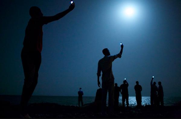 Inmigrantes africanos en la costa de Djibouti, buscan señal con sus teléfonos móviles para intentar comunicarse con sus familiares. Fotografía ganadora del World Press Photo 2014 de John Stanmeyer