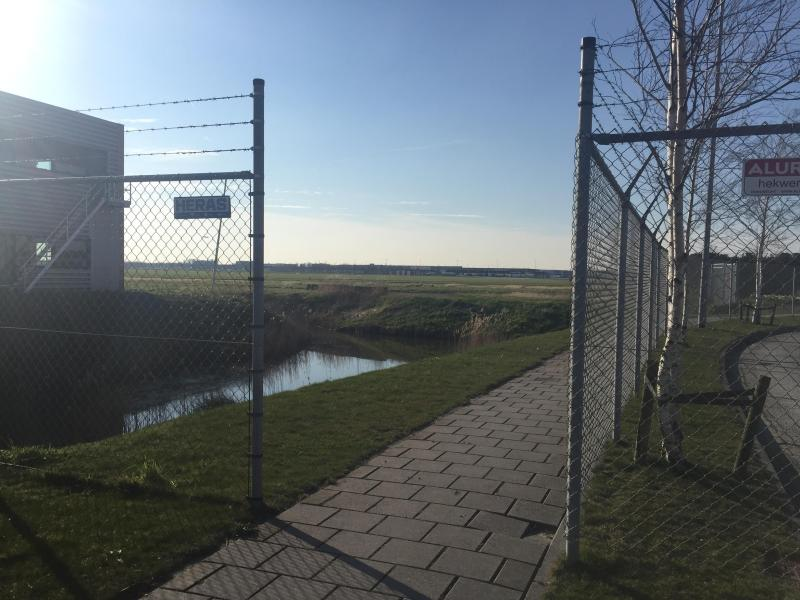 Below, Gated entrance to the memorial, at the end of the pathway a circle of dried, pine bushes hid the memorial. 03/04/2016 door Octavia Aronne (Unwanted souls, unwanted thoughts: Memorialization, Change, and Meaning of the Schiphol-Oost Detention Centre Fire)