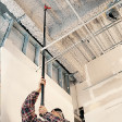 Man uses pole to reach high ceiling without a ladder