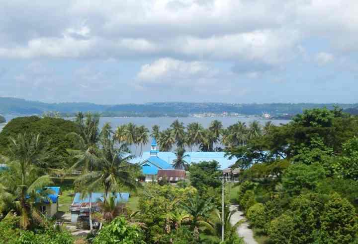 Pemandangan dari Gereja baru di Pulau Mansinam. Bangunan biru merupakan gereja lama.