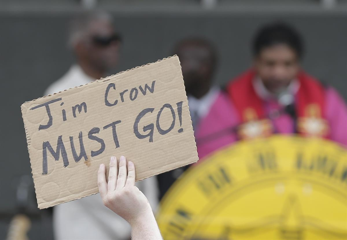 A man holds a protest sign as Rev. William Barber II speaks at a rally in Winston-Salem, N.C. on July 13, 2015 after the beginning of a voting rights trial (AP Photo/Chuck Burton).