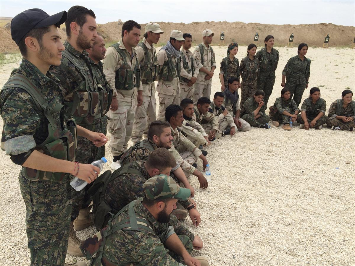 Members of what the U.S. calls the Syrian Democratic Forces gather after a training session at a firing range in northern Syria. May 21, 2016,(AP Photo/Robert Burns)