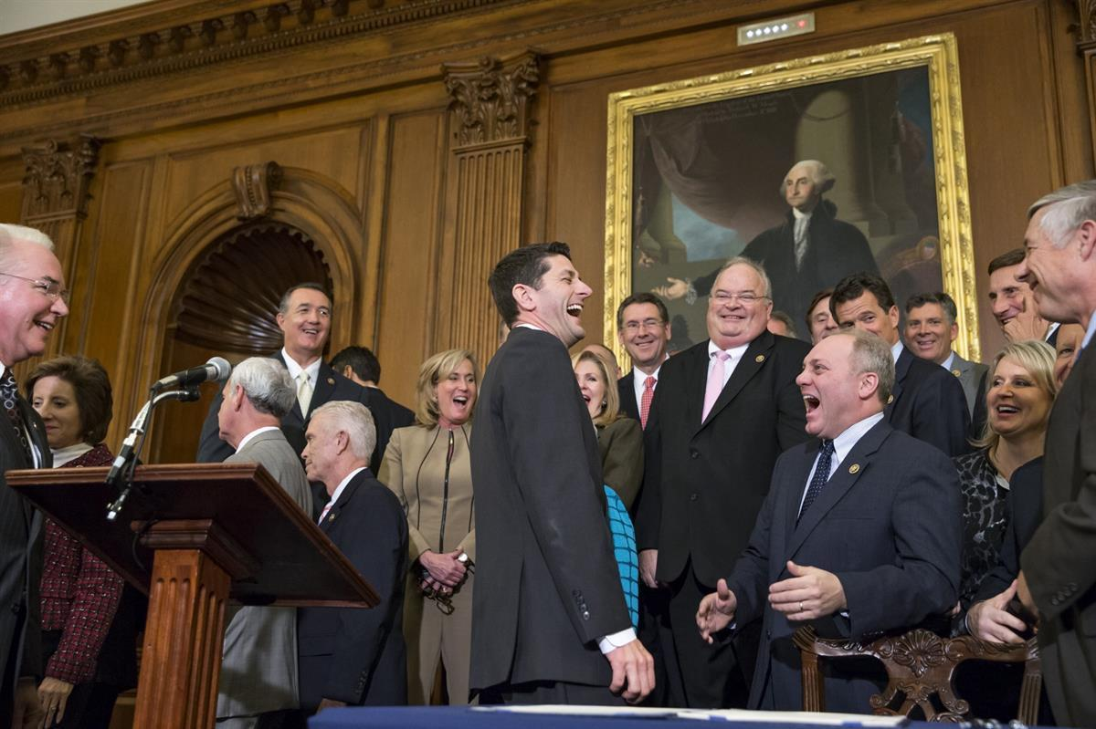 Speaker of the House Paul Ryan, R-Wis., left, laughs with Majority Whip Steve Scalise, R-La., center right, just after Ryan signed a bill designed to eliminate key parts of President Barack Obama's health care law. Thursday, Jan. 7, 2016. (AP Photo/J. Scott Applewhite)
