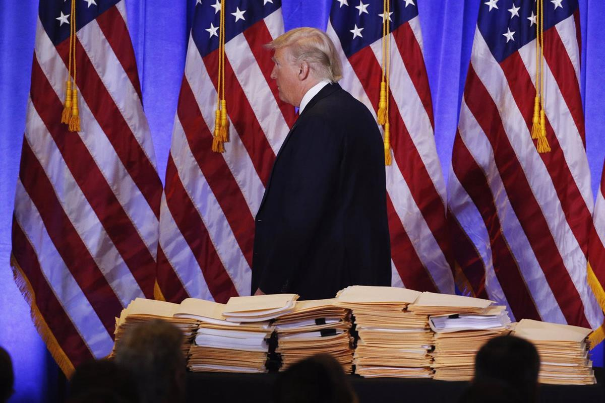 Donald Trump walks past papers that he said were related to the transfer of Trump Organization operations to his sons at a January 11th press conference (Reuters)