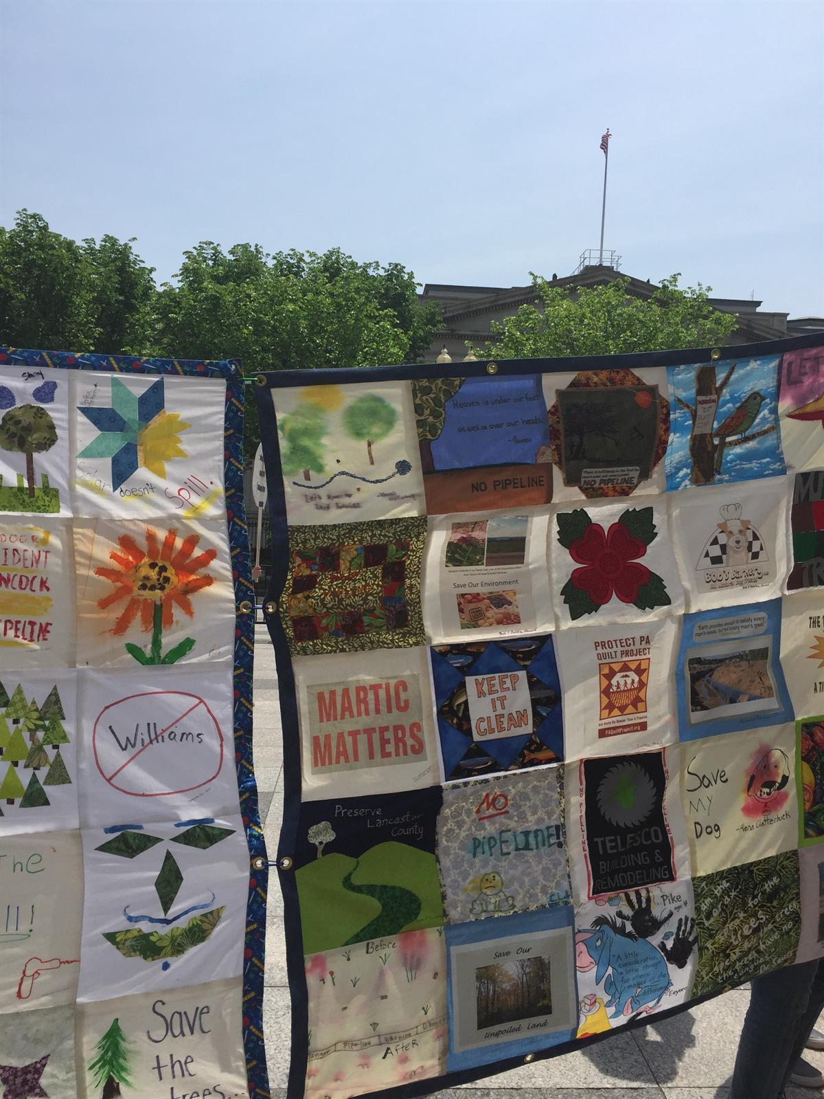 A large quilt depicting different climateslogans.