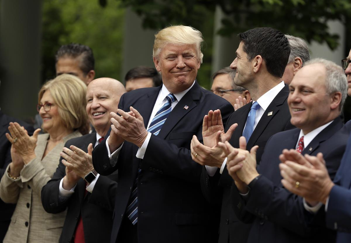 President Donald Trump, flanked by House Ways and Means Committee Chairman Rep. Kevin Brady, R-Texas, and House Speaker Paul Ryan of Wis., applaud in the Rose Garden of the White House in Washington, Thursday, May 4, 2017, after the House pushed through a health care bill. (AP Photo/Evan Vucci)