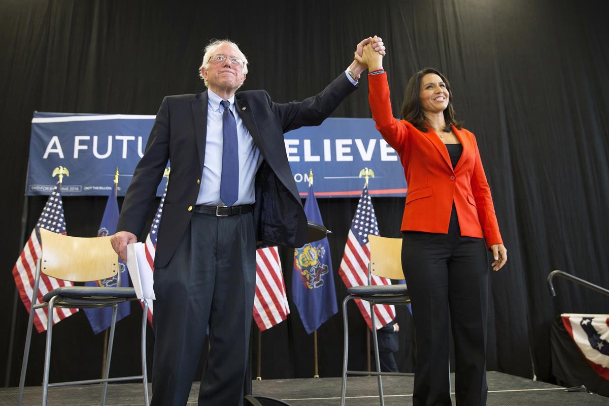Senator Bernie Sanders, I-Vt., holds hands with Rep. Tulsi Gabbard, D-Hawaii, during a town hall campaign event at Gettysburg College, in Gettysburg, Pa. — April 22, 2016 (AP/Evan Vucci)
