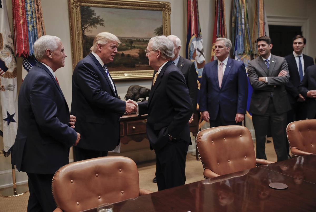 President Donald Trump shakes hands with Senate Majority Leader Mitch McConnell (R-KY), center. Also in the room are from left, Vice President Mike Pence, Senate Majority Whip John Cornyn (R-TX), House Majority Leader Kevin McCarthy (R-CA), House Speaker Paul Ryan (R-WI)., and Senior adviser Jared Kushner — June 6, 2017 (AP)