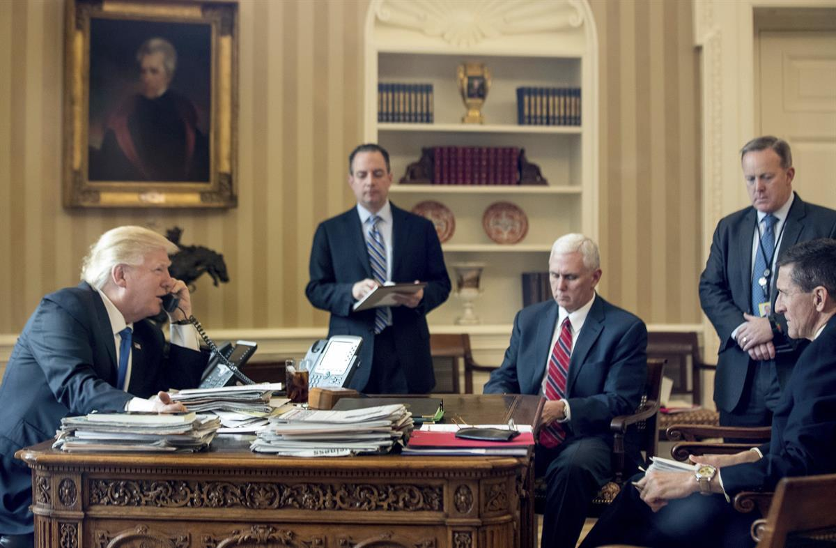 President Donald Trump, accompanied by, from second from left, Chief of Staff Reince Priebus, Vice President Mike Pence, White House press secretary Sean Spicer and former National Security Adviser Michael Flynn, speaks on the phone with with Russian President Vladimir Putin, Saturday, Jan. 28, 2017, in the Oval Office at the White House in Washington. (AP Photo/Andrew Harnik)