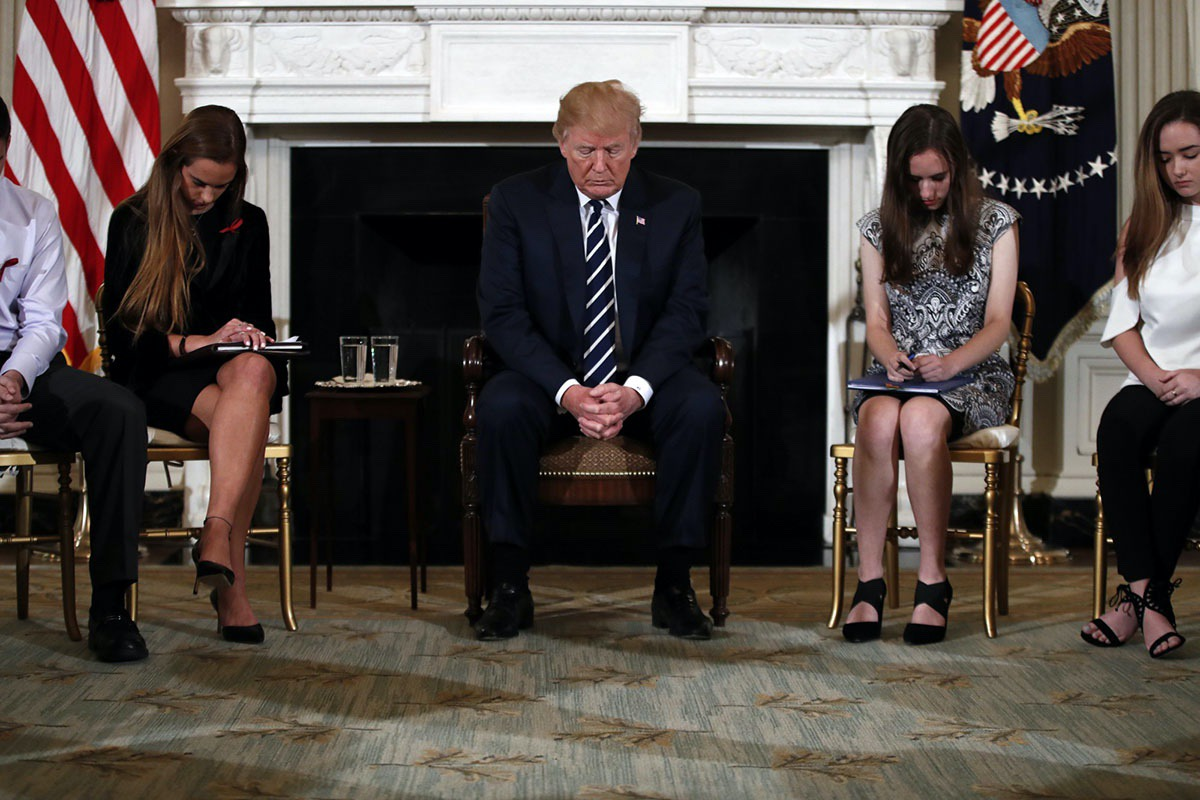 President Donald Trump bows his head during an opening prayer at the start of a listening session with high school students and teachers in the State Dining Room of the White House in Washington, Wednesday, Feb. 21, 2018. (AP Photo/Carolyn Kaster)
