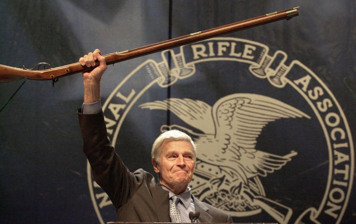 NRA president Charlton Heston holds up a musket as he tells the 5000 plus members attending the 129th Annual Meeting & Exhibit in Charlotte, NC — May 20, 2000 (AP Photo/Ric Feld)
