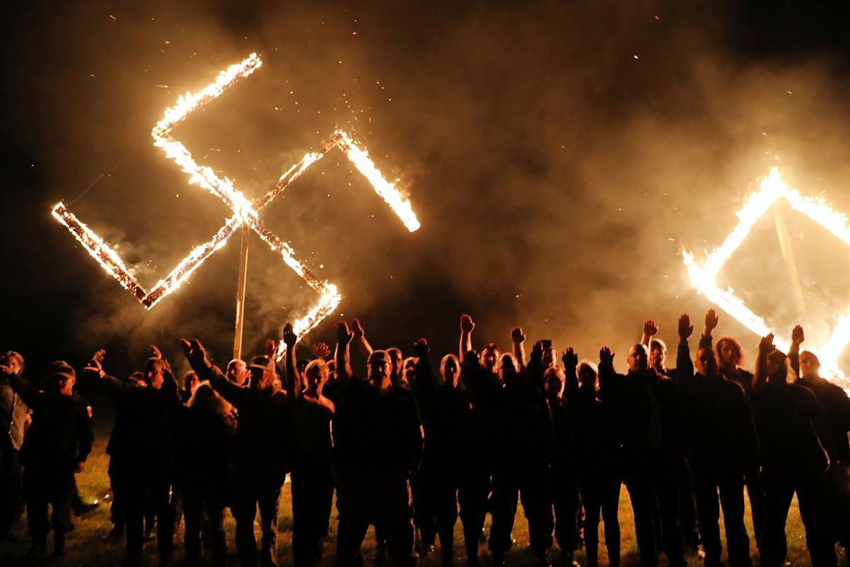 Members of the National Socialist Movement, one of the largest neo-Nazi groups in the US, hold a swastika burning after a rally on April 21, 2018 in Draketown, Georgia (Spencer Platt—GettyImages)