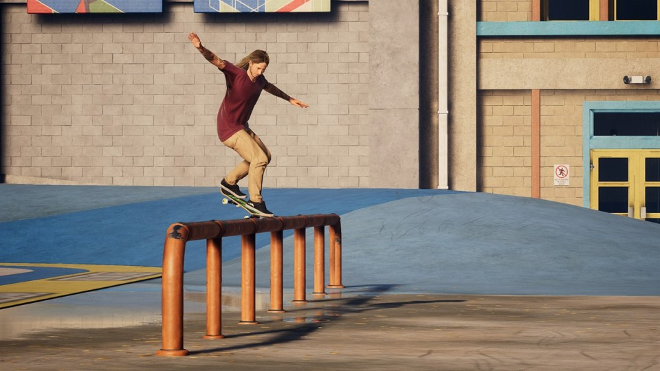 A skater grinding over an orangeskatebar. Their hands are balancing in the air