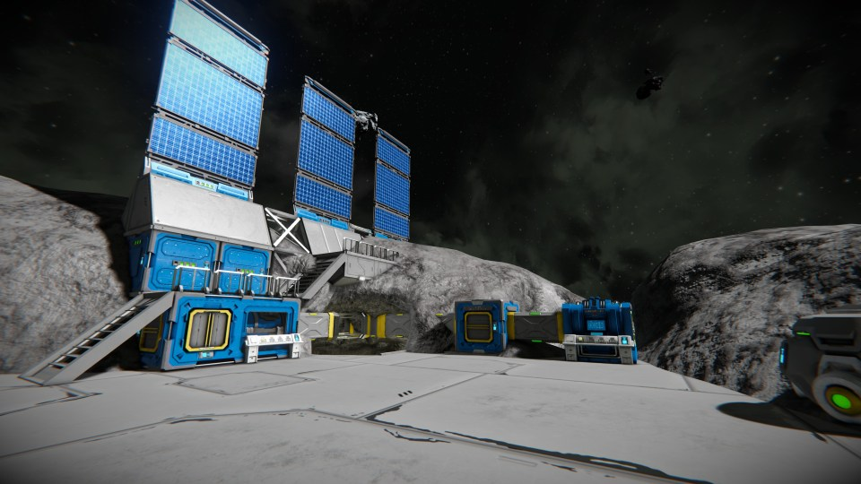 A small base built into an asteroid, with stairs, solar panels, and several machines connected by a pipeline.