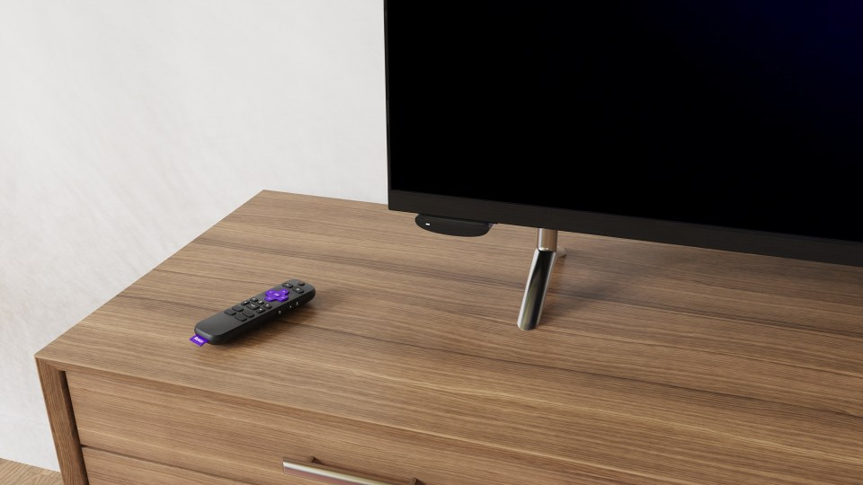 Roku Express 4K remote and TV sat on a chest of drawers, Roku Express 4K device attached to left underside of TV