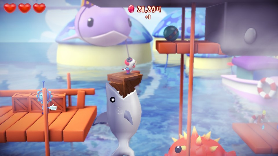 Ayo standing on a box while a shark is jumping to get him. He is above an ocean