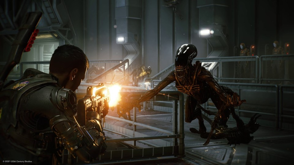 A xenomorph pounces towards a space marine who opens fire on it with his gun.