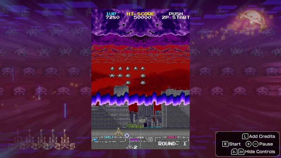 A purple sky which turns into red with skyscrapers in the background, invaders descend the screen in the middle with a defender at the bottom with a 'shield' bar