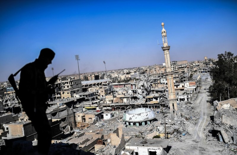 A member of the Syrian Democratic Forces, backed by U.S. special forces, talks on the radio near Raqqa's stadium as they clear the last positions on the front line on Oct. 16, 2017. The city was an important Islamic State group stronghold. Bulent Kilic/AFP/Getty Images