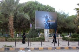 """HVERDAGEN I BYEN: Kvinner i niqab går her forbi IS-propaganda i en park i Raqqa, 1. november 2014. På plakaten står det, grovt oversatt, at """"vi skal vinne fram, tross den globale koallisjonen"""". Foto: Str / Rmc / AFP Photo / NTB Scanpix"""