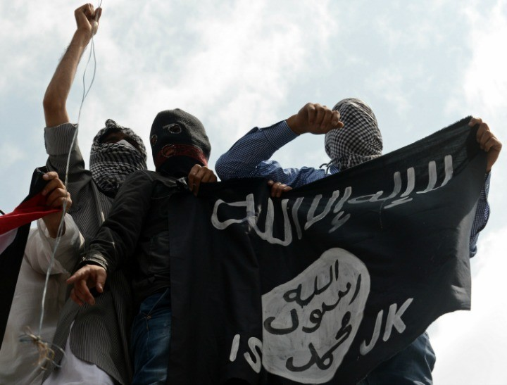 Young men fly the ISIS flag.
