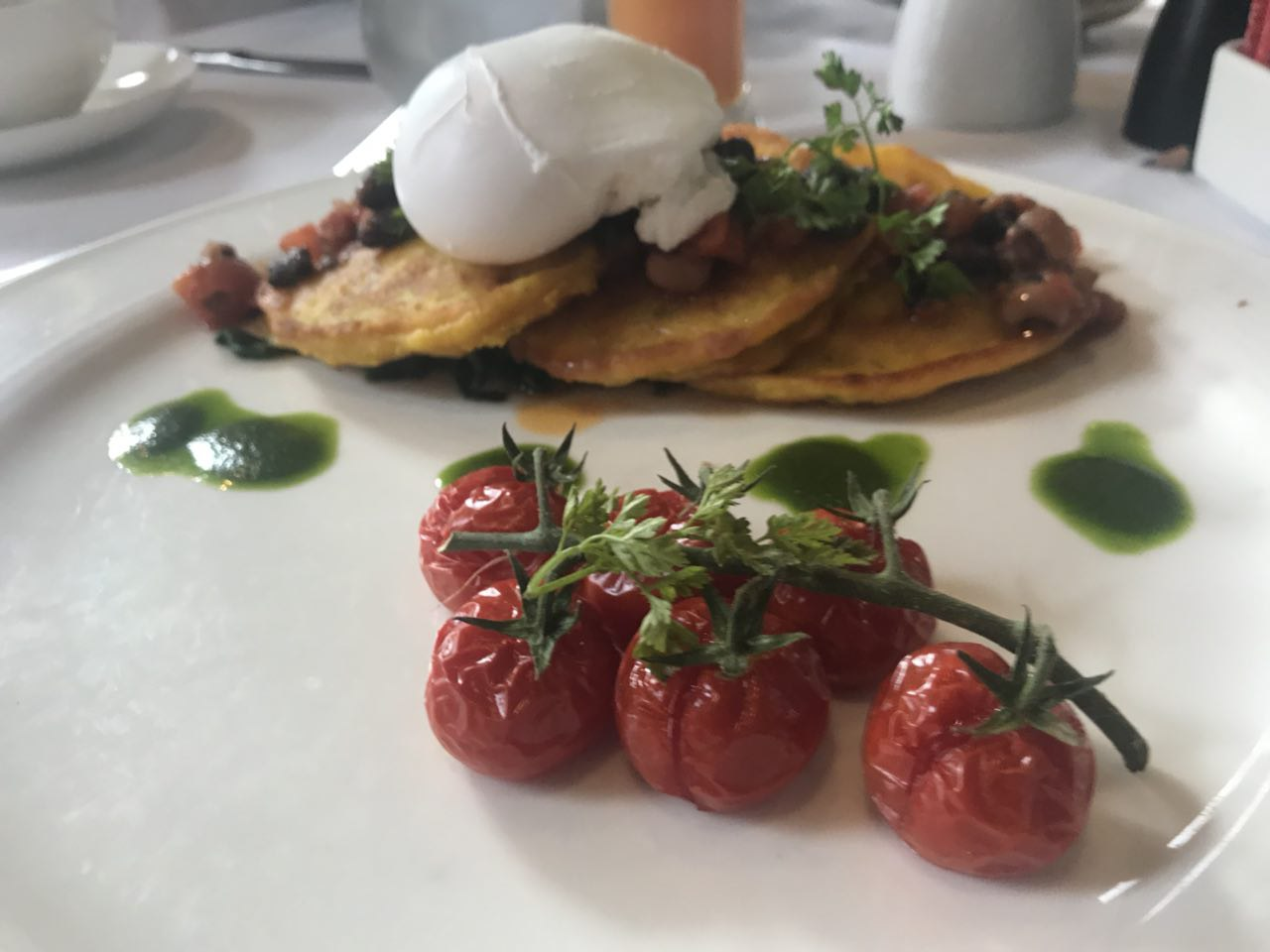 Eleanor's sweetcorn and zucchini hotcakes, with roasted tomatoes, spinach, red pepper and black bean salsa and a poached egg
