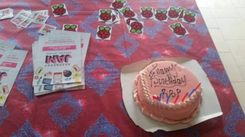 "A round pink-iced cake decorated with the words ""Happy Birthday RBP"" and six candles, on a table beside Raspberry Pi stickers, Raspberry Jam stickers and Raspberry Jam fliers"