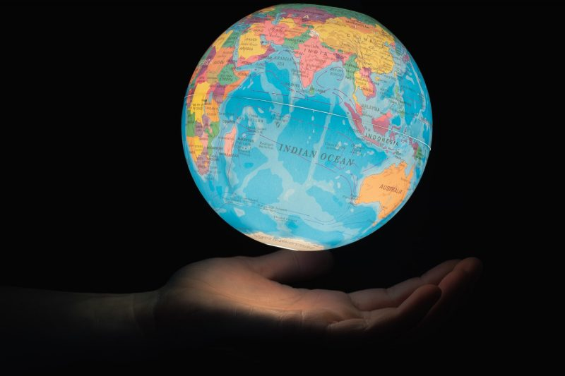 A glowing globe floating above an open hand in the dark