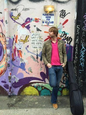 Photo of Lawrence Bray leaning against a graffitied wall.