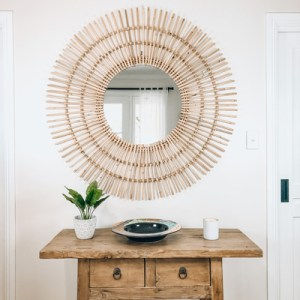 rattan sun mirror above table