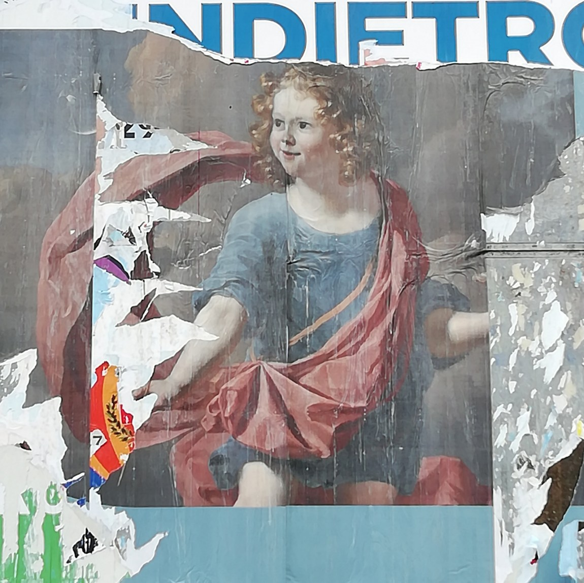 photograph of billboard with posters peeling to reveal previous layers, including a young child with curly hair