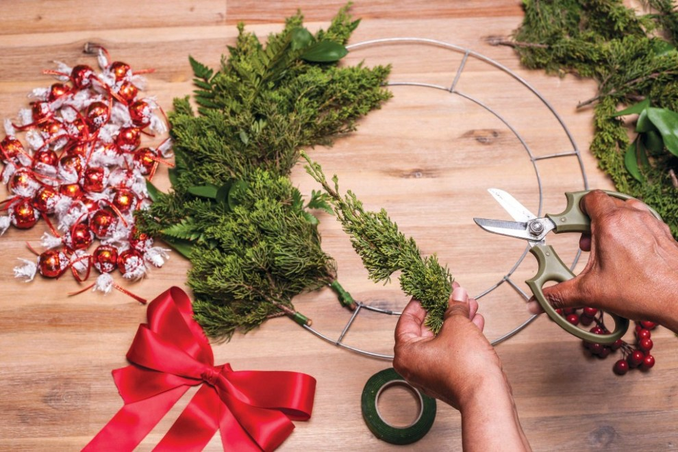 2. Assemble wreath by taking pieces of cut foliage and tying them with tape to the frame. Follow the natural curve of the branches.