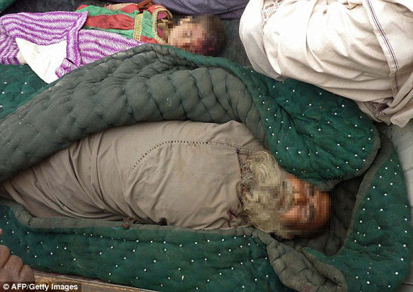 The bodies of an elderly Afghan man and a child killed in the Alkozai village of Panjwayi district are shown wrapped in blankets