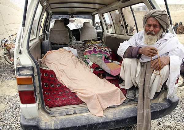 An elderly Afghan man sits next to the covered body of a person who was killed early today by a U.S. service member