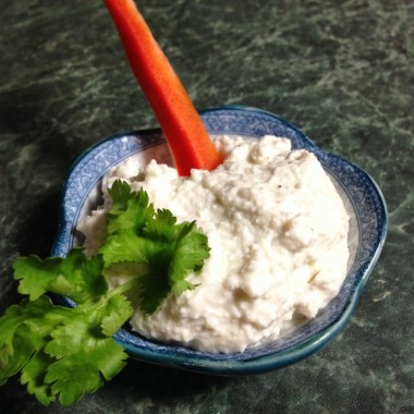 Plate with Vegan Sour Cream with garnish of cilantro and carrot