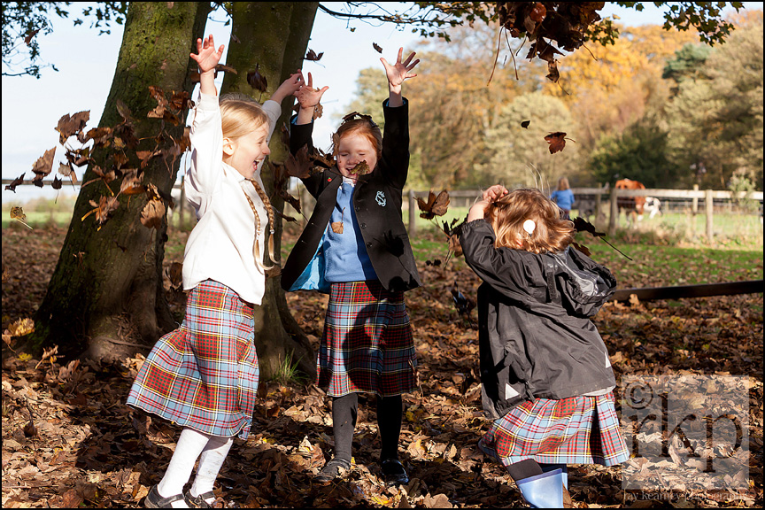 Junior school children playing with leaves
