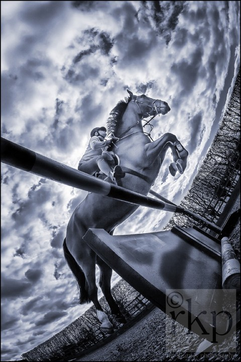 Horse jumping post with dramatic sky